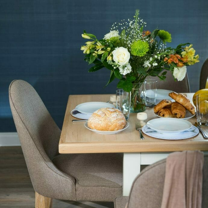 Brown Dining Chairs against Deep blue wallpaper by Jane Churchill