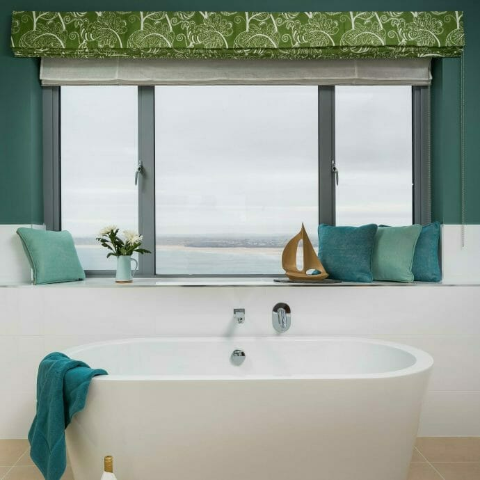 Forest Green Brunschwig and fils roman blind in bathroom with sea view.